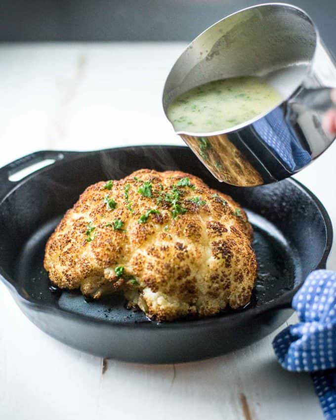 pouring butter sauce over Whole Roasted Cauliflower