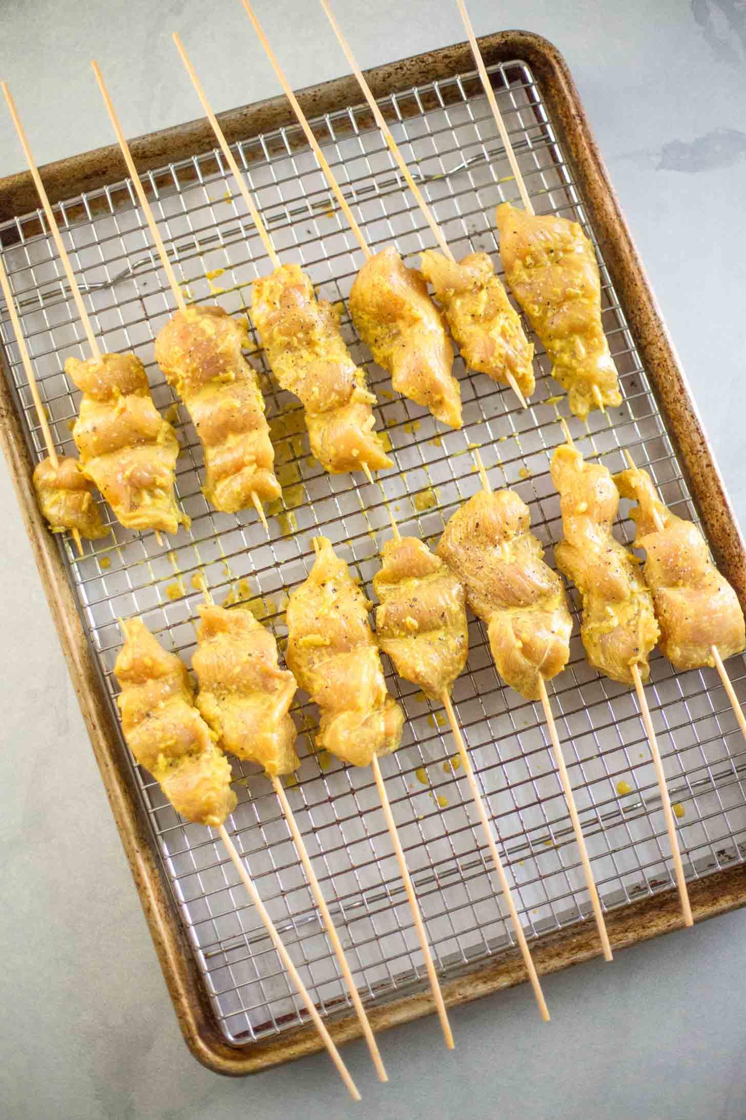 chicken satay on skewers on a sheet pan