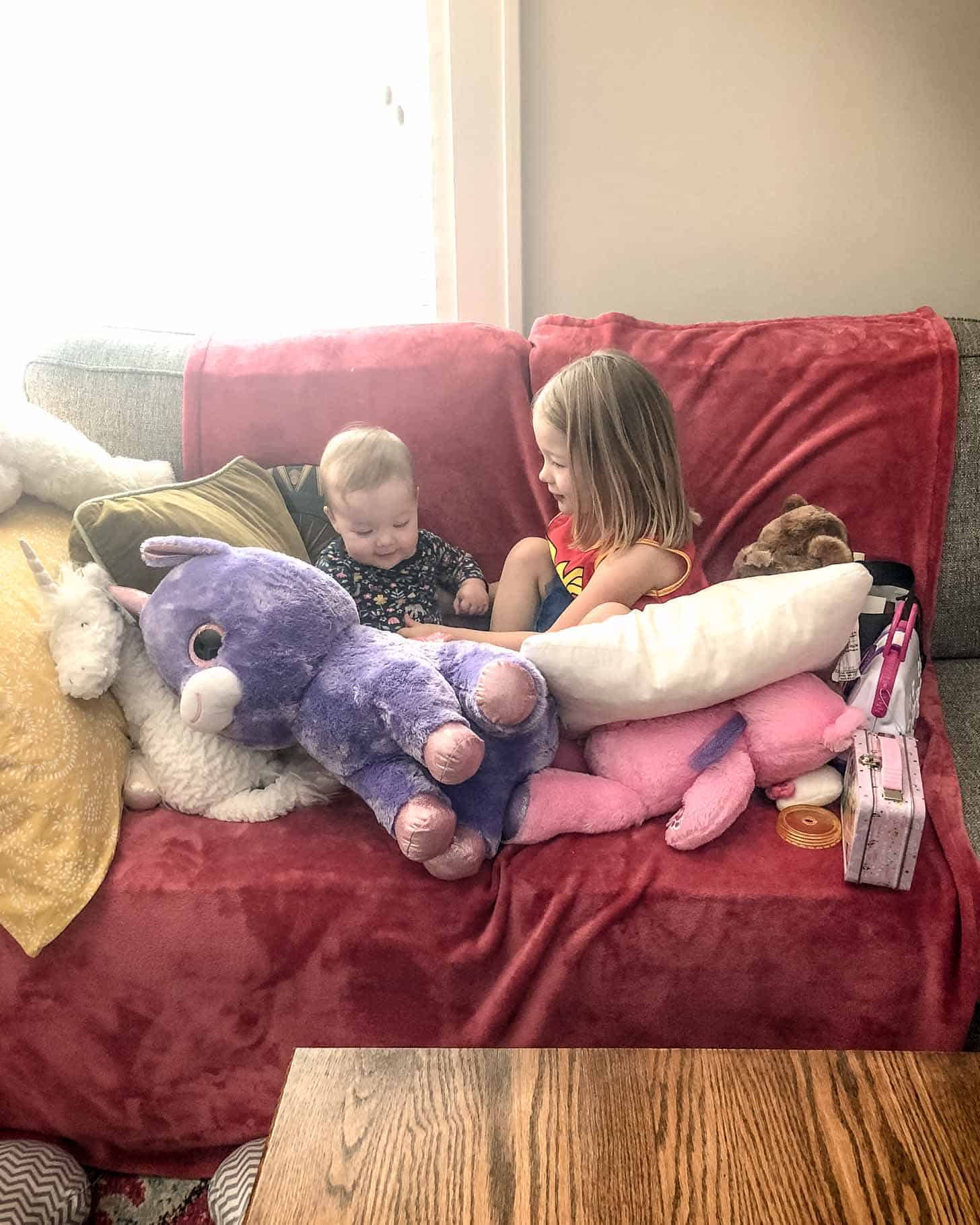 a girl and a baby in a couch fort