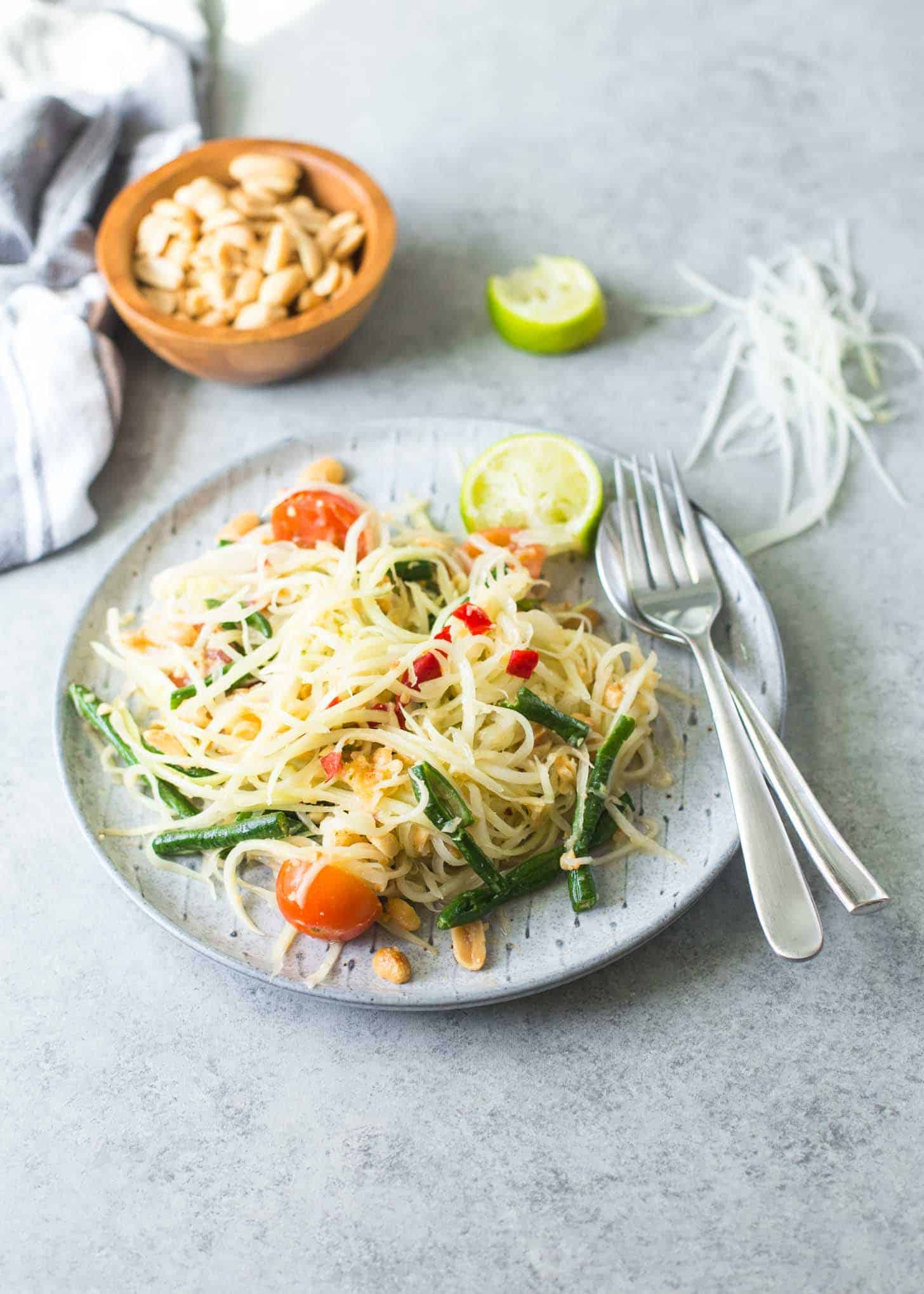 Green Papaya Salad (Som Tam) on a white plate with a fork