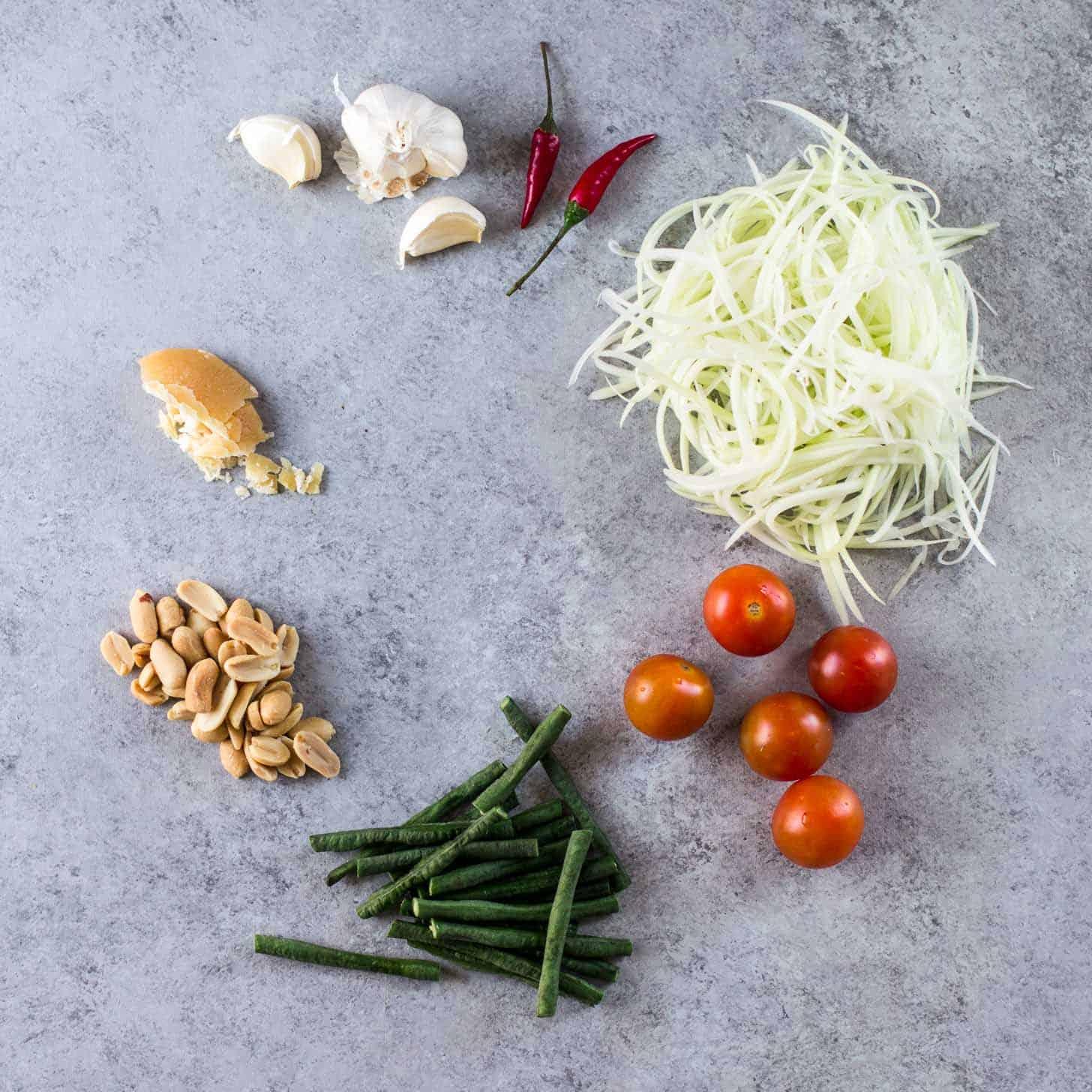 Ingredients for Green Papaya Salad on a grey countertop
