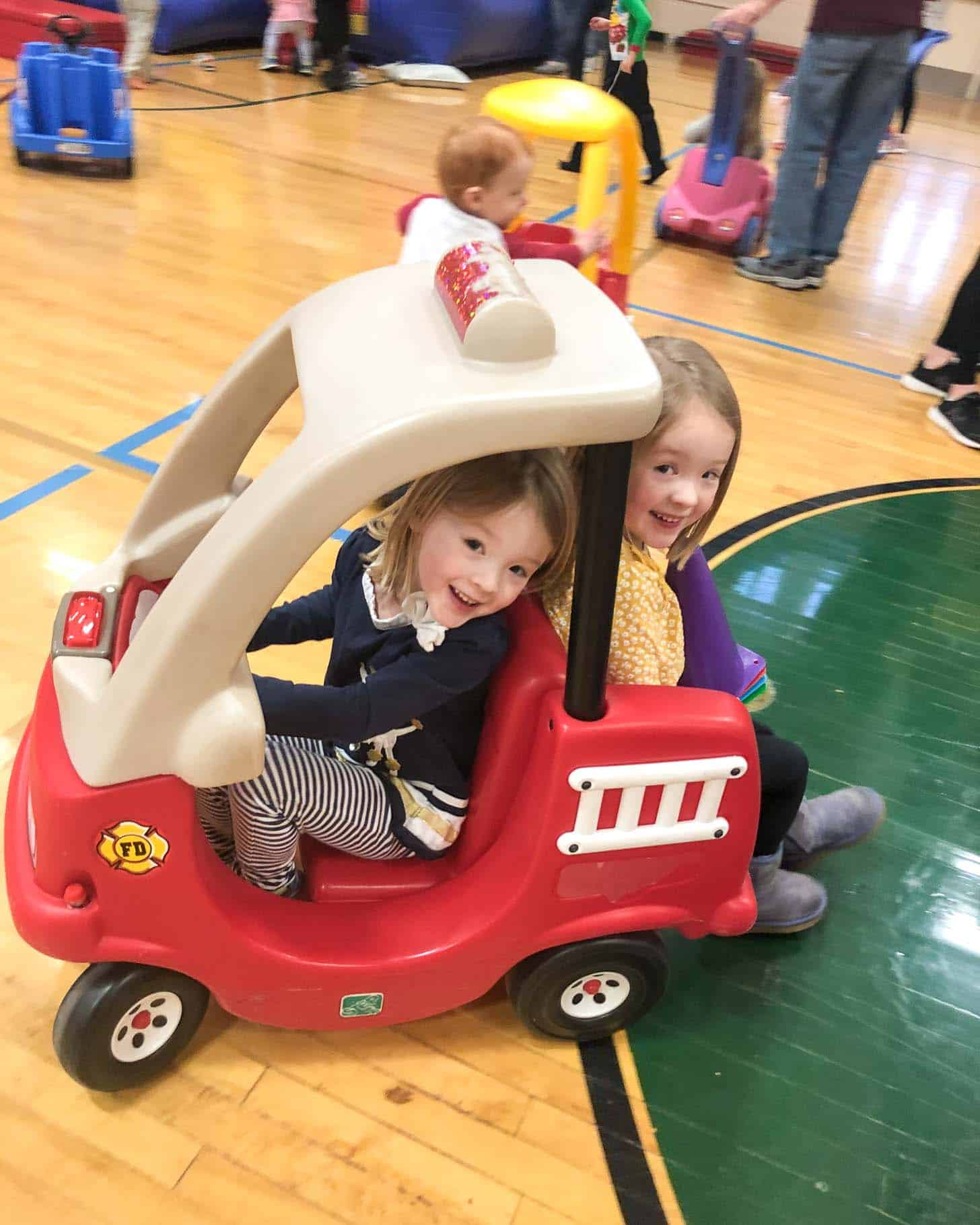 two little girls in a play car