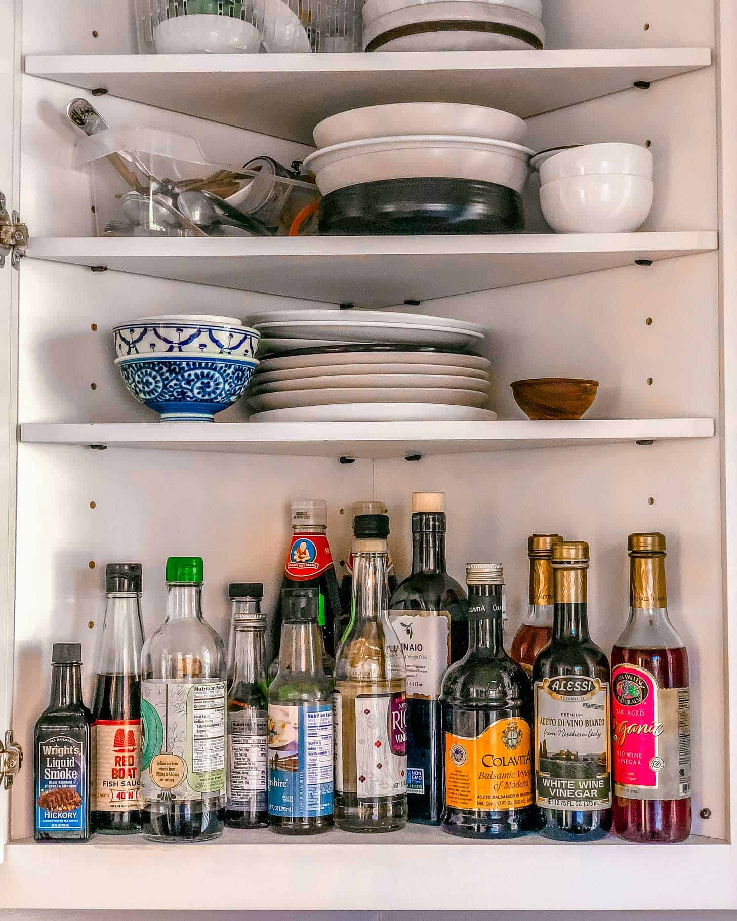 an open corner cabinet with bottles and plates