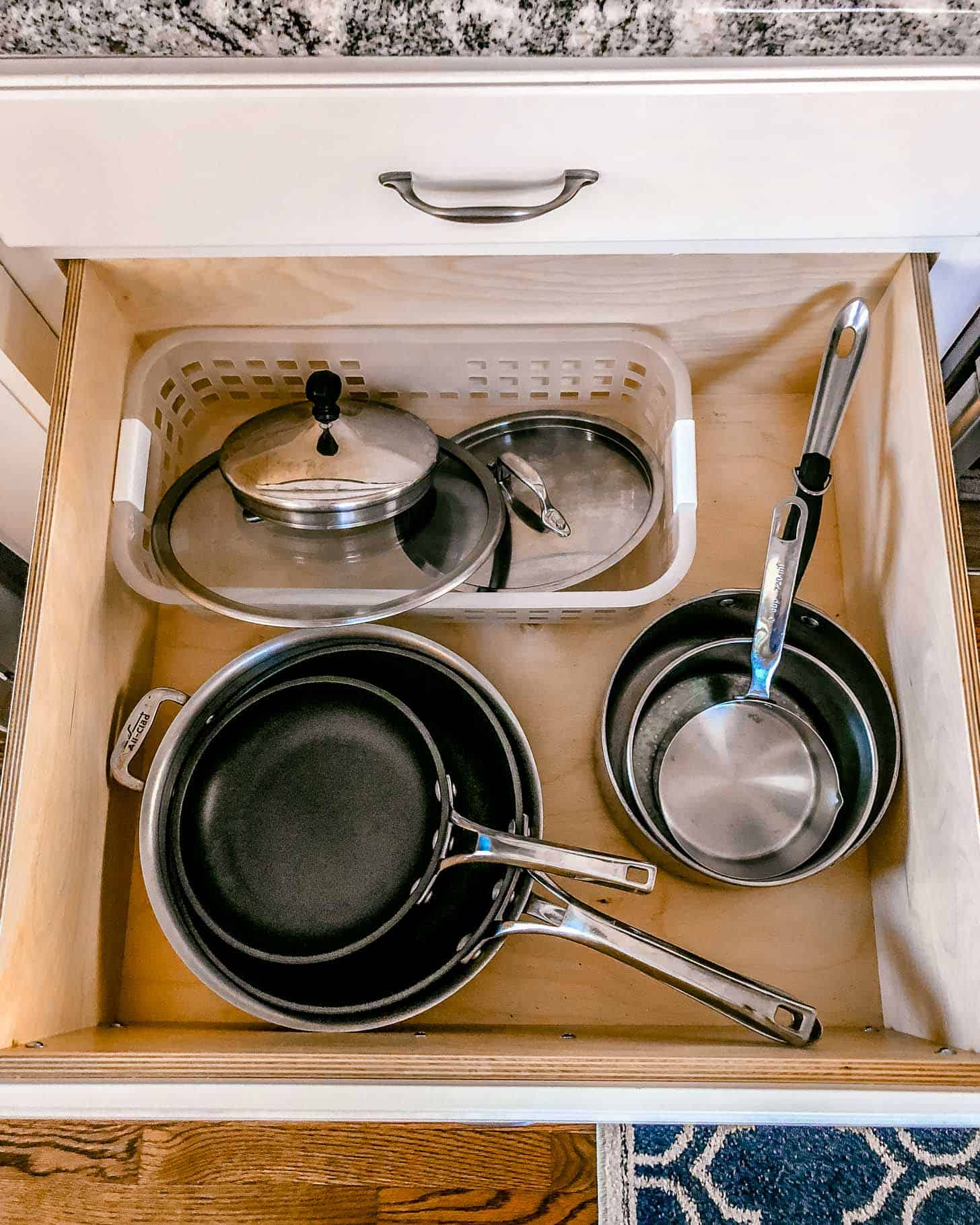 a large drawer with pots and pans