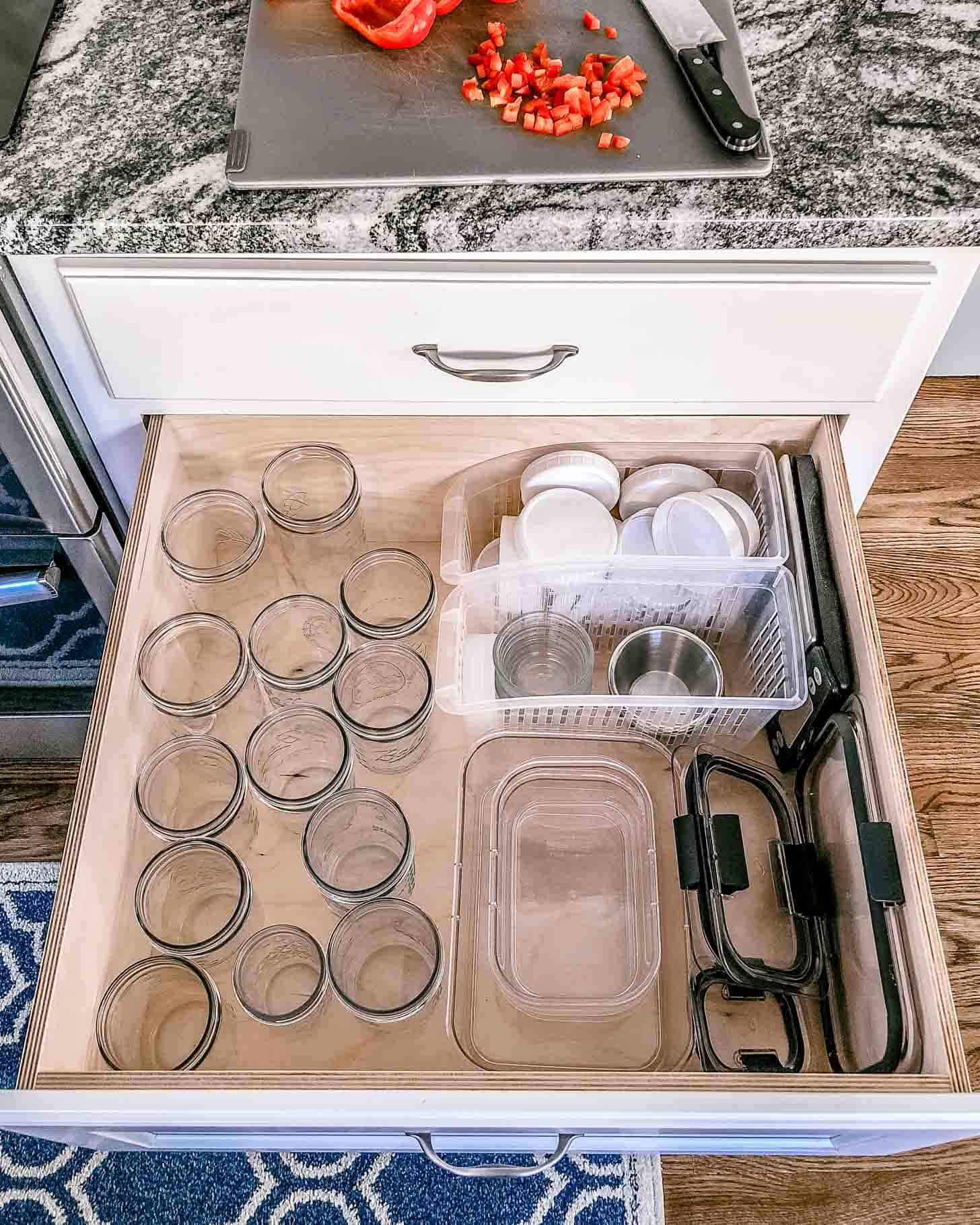 a drawer with plastic containers and glass jars