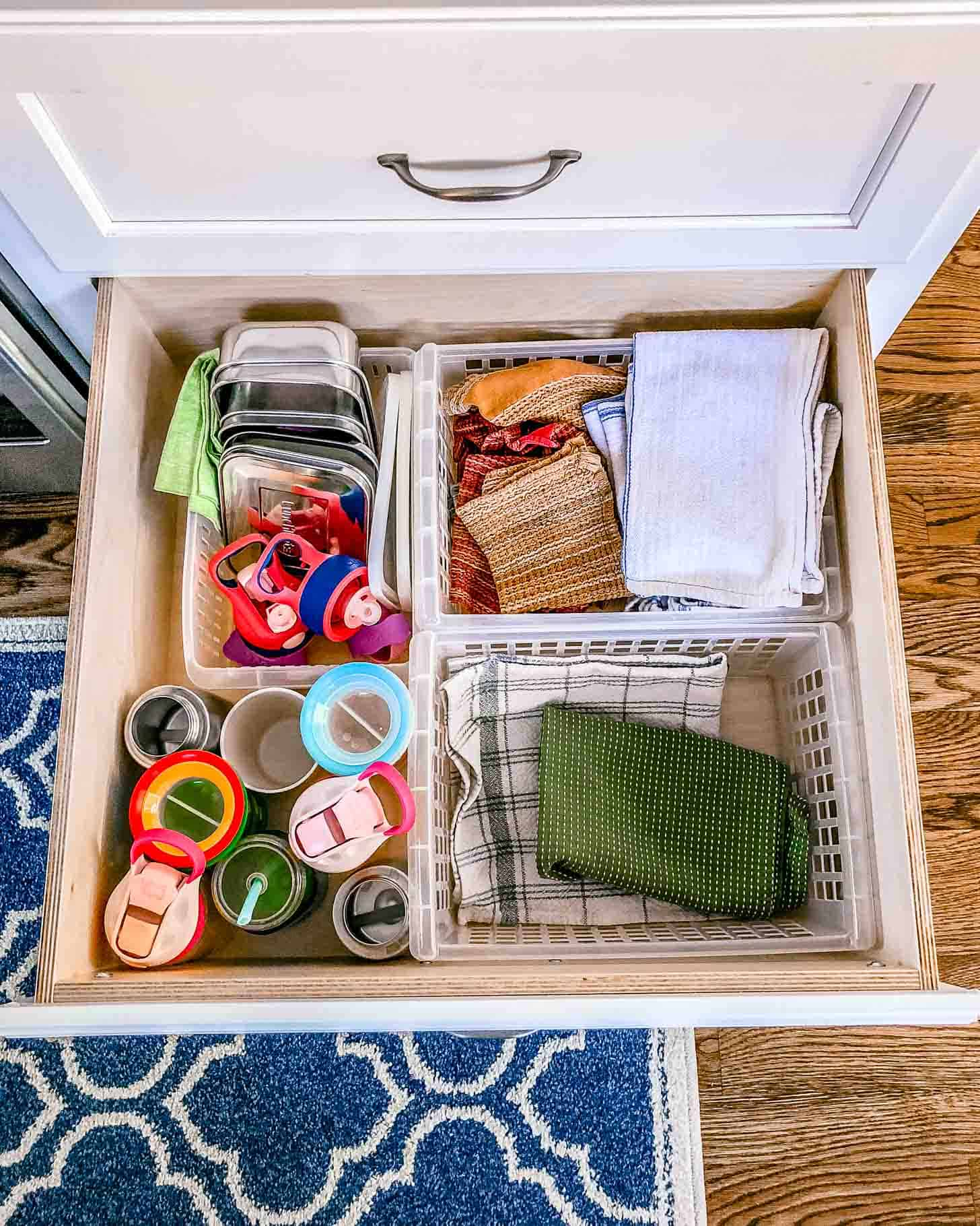 a large drawer with cups and dish towels