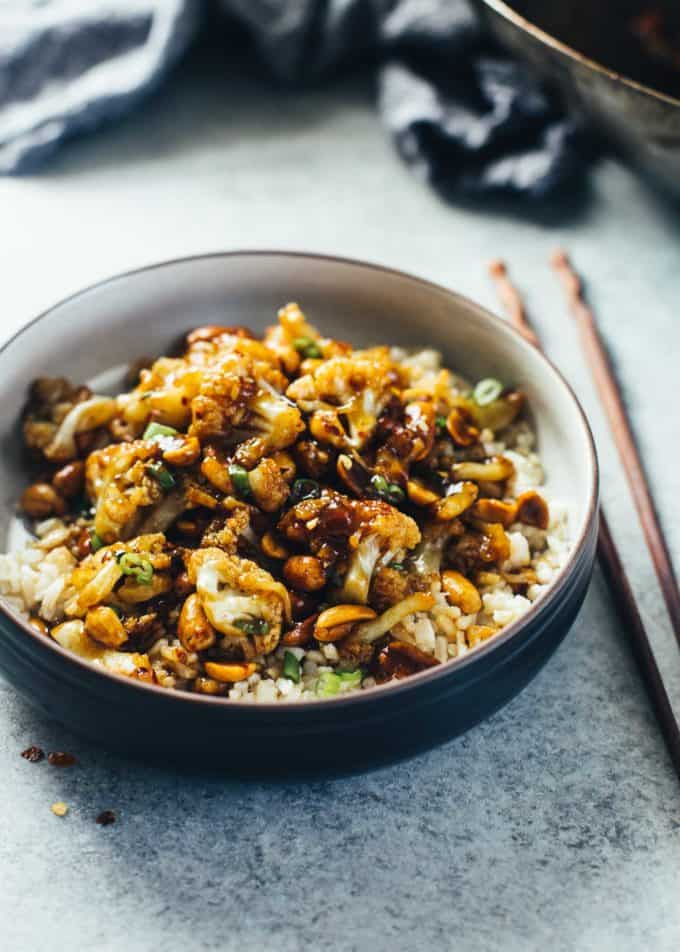 Kung Pao Cauliflower over rice in a black bowl