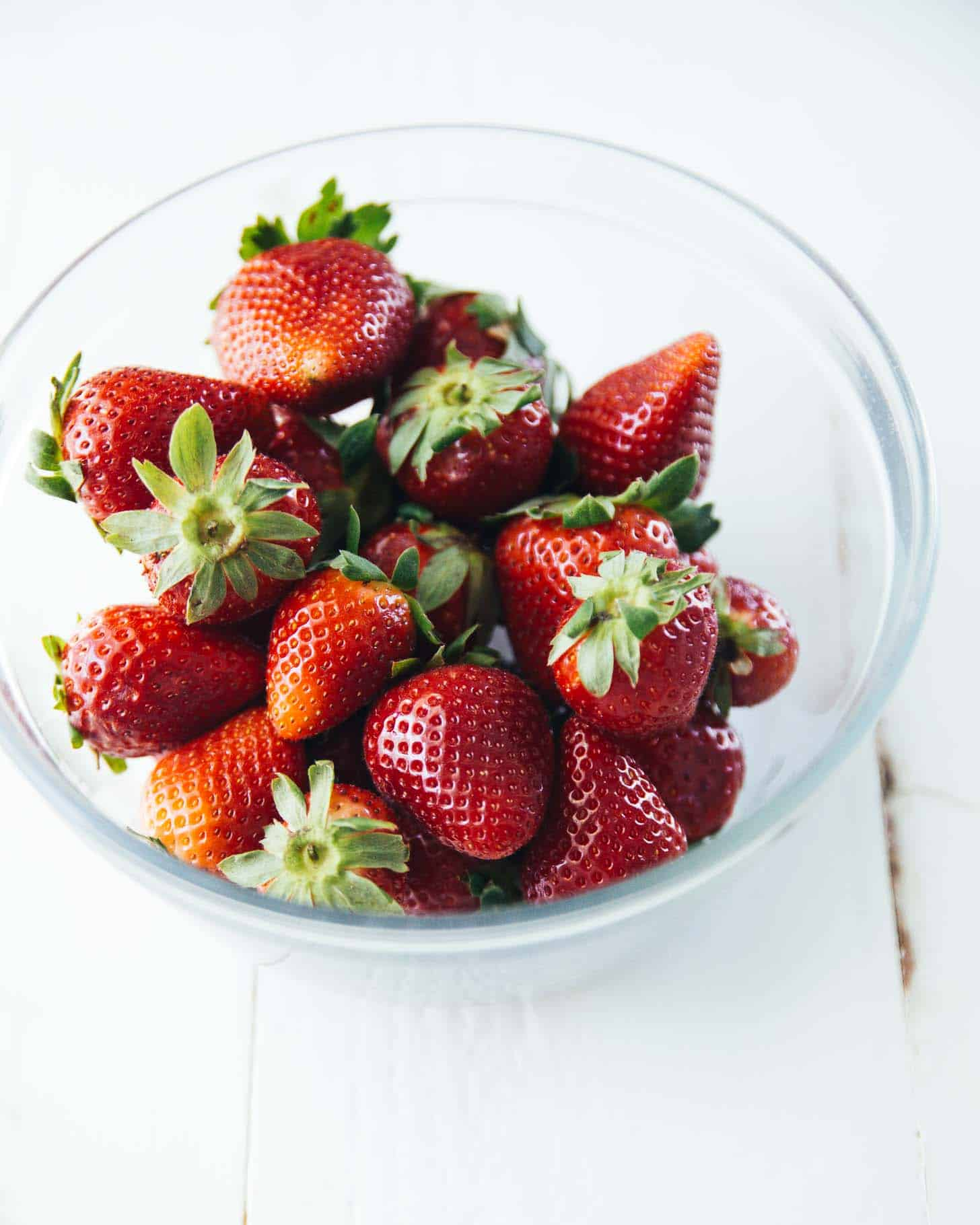 fresh strawberries in a clear bowl