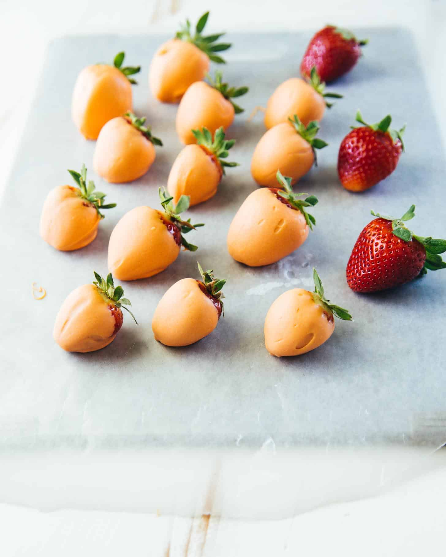 orange dipped strawberries on a sheet of parchment paper