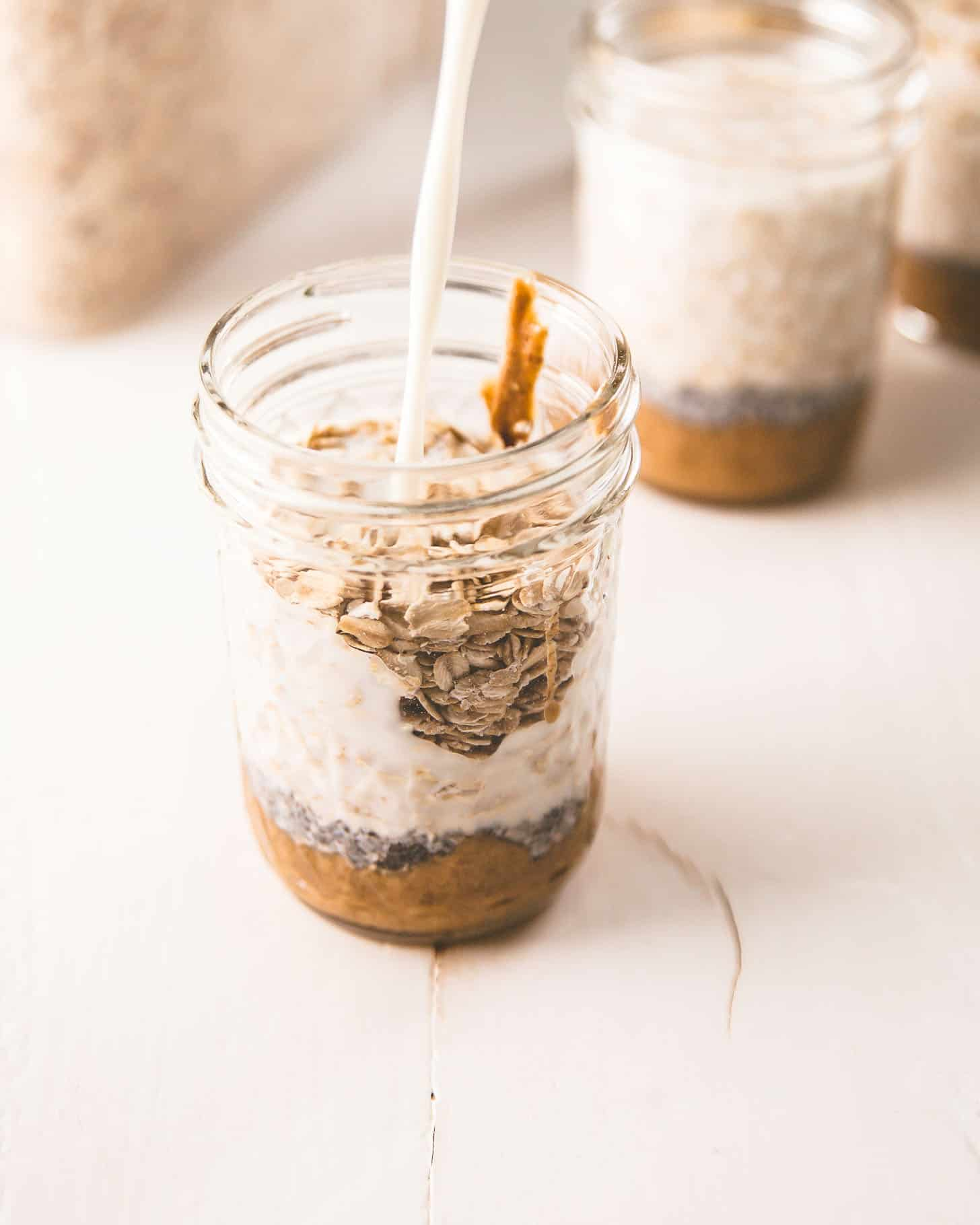 adding milk to overnight oats in a mason jar