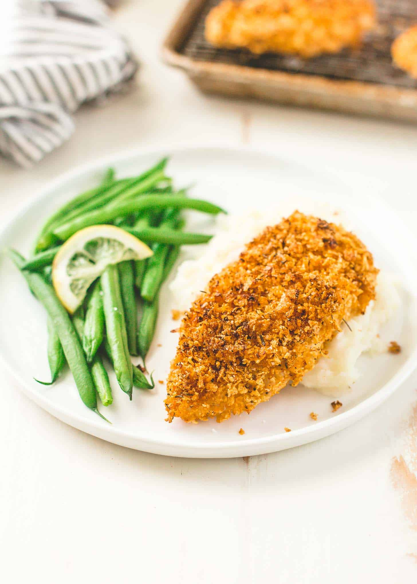 Crispy Baked Cornflake Chicken on a plate with mashed potatoes and green beans