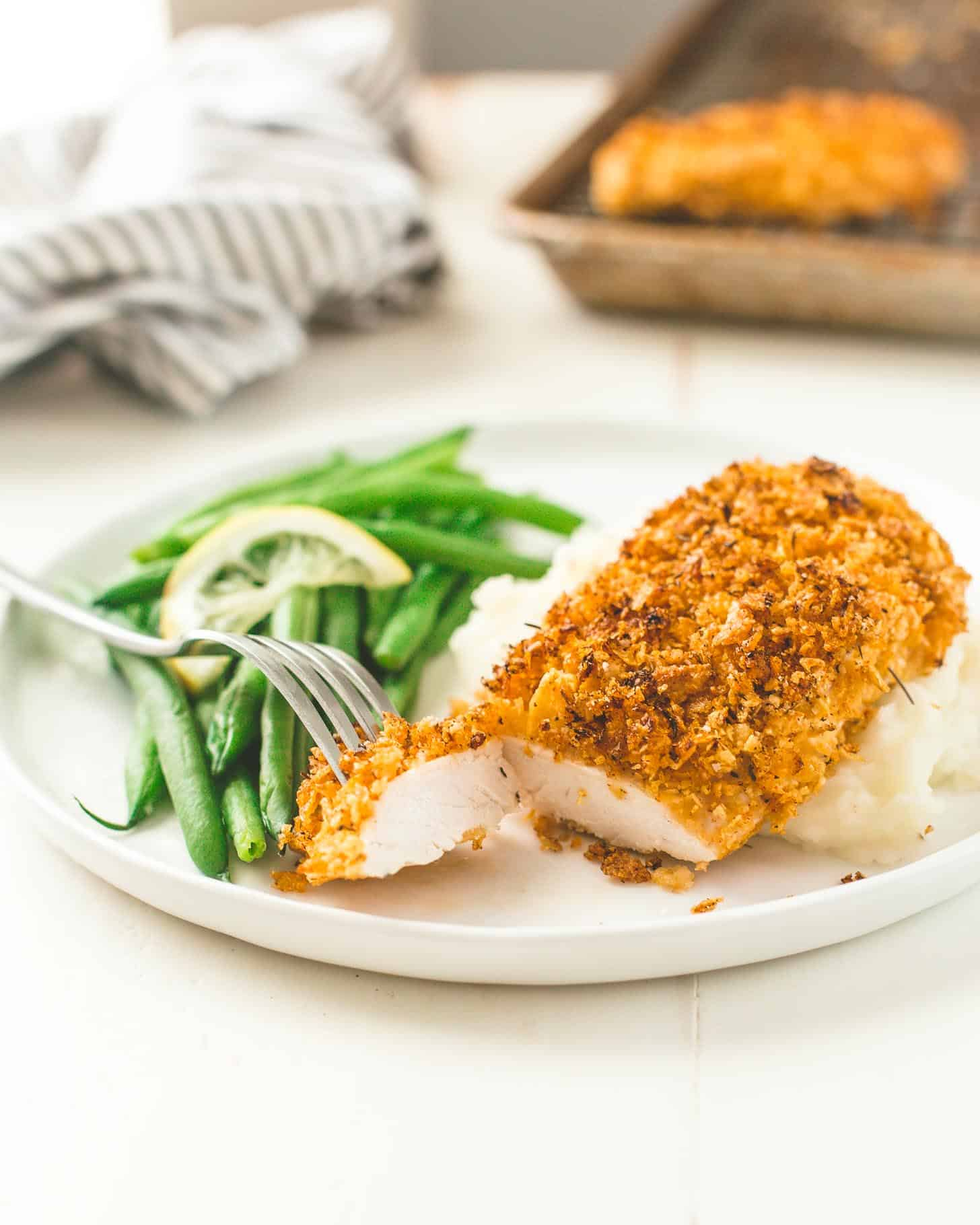 Crispy Baked Cornflake Chicken on a white plate with green beans and mashed potatoes