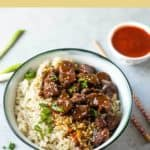 Instant Pot Korean Beef and Brown Rice in a bowl with chopsticks and spicy Korean sauce