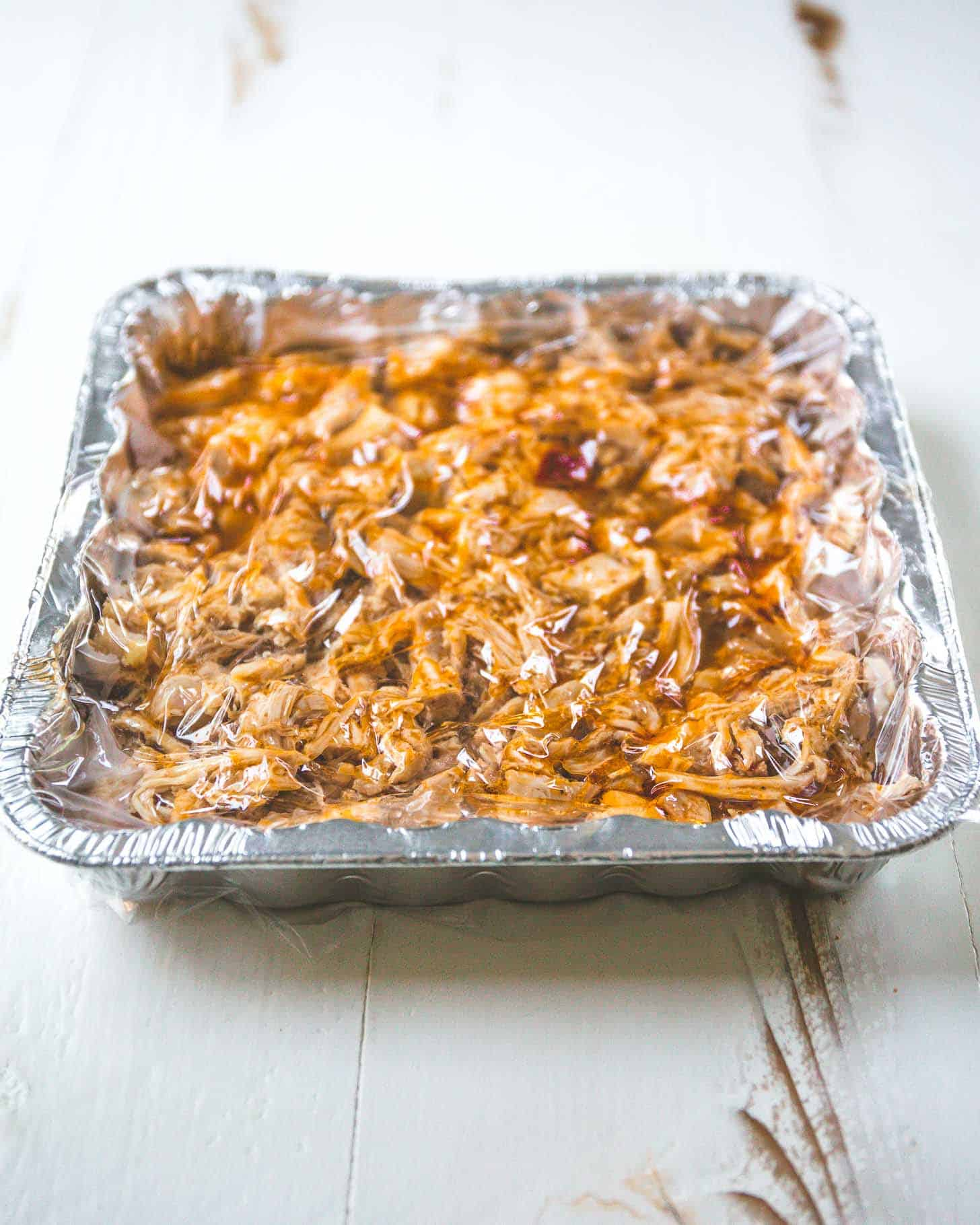 BBQ Pulled Chicken in a silver baking pan topped with plastic wrap