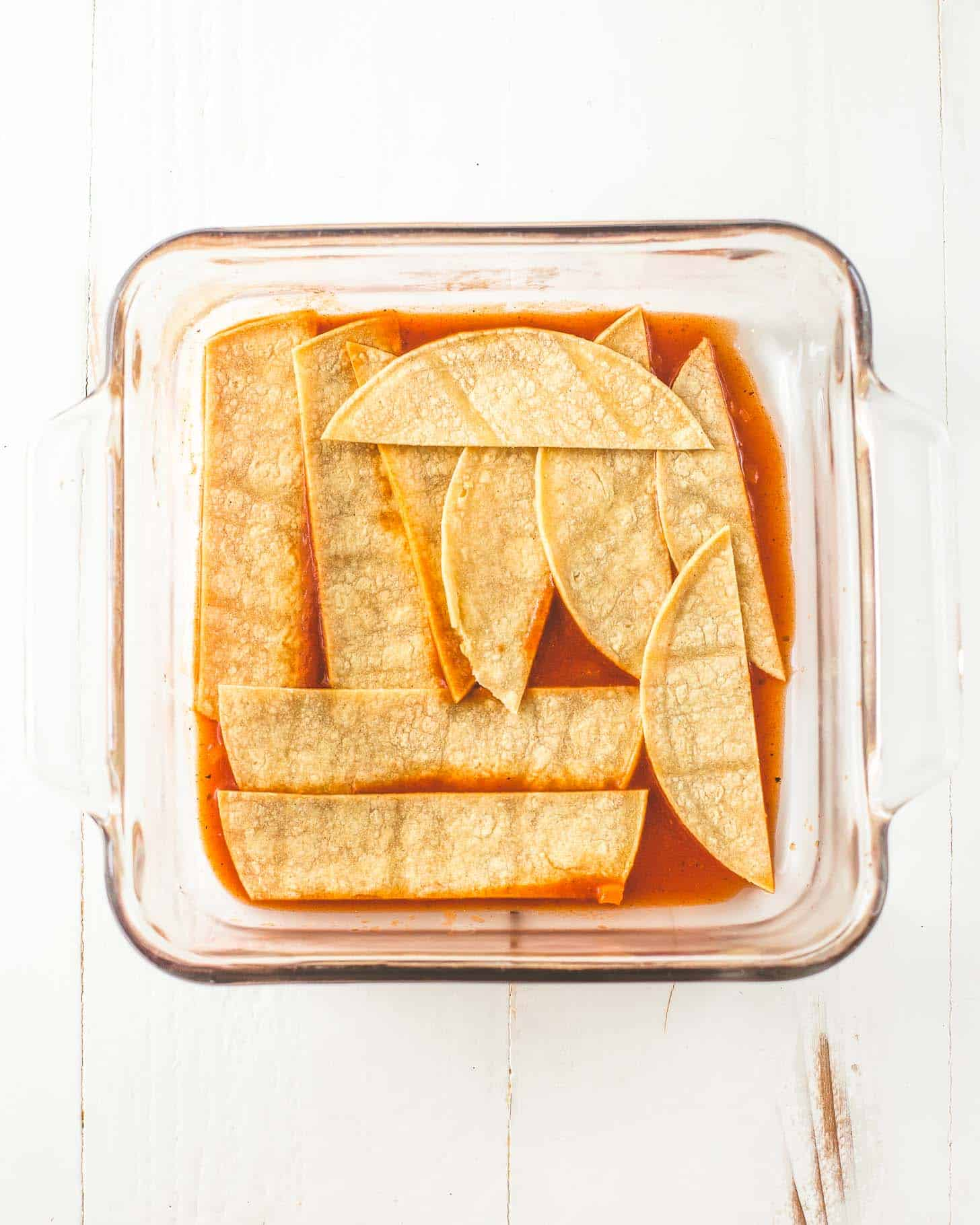 tortillas and enchilada sauce in a square baking dish