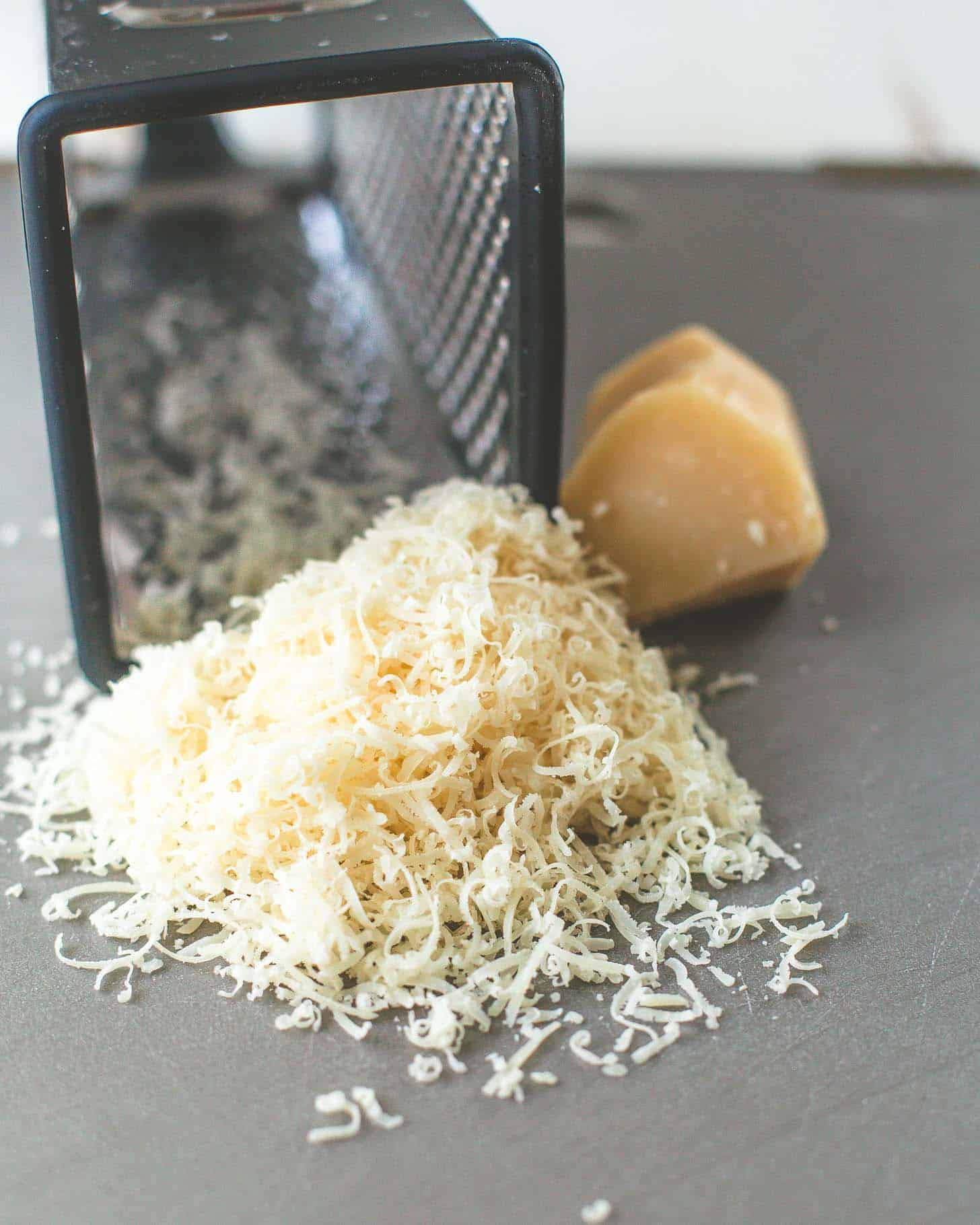 shredded parmesan and a box grater on a table