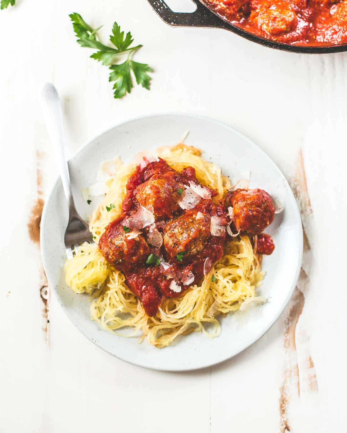 Italian Turkey Meatballs over pasta on a white plate