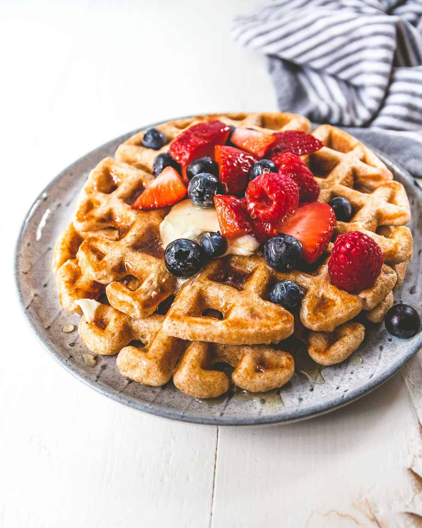 Whole Wheat Waffles on a white plate and topped with berries