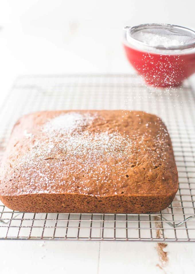 topping Applesauce Cake with powdered sugar on a cooling rack