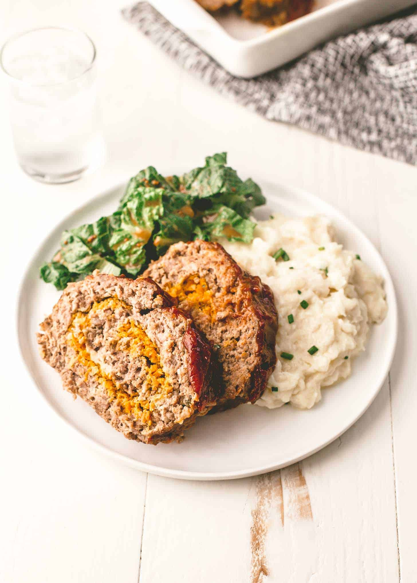 Classic Meatloaf on a white plate with mashed potatoes