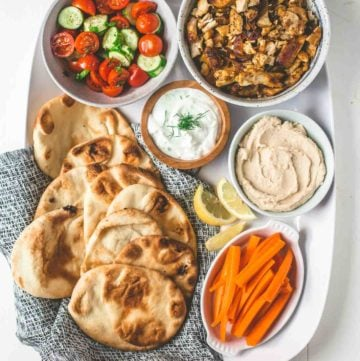 naan, shawarma and toppings on a white tray