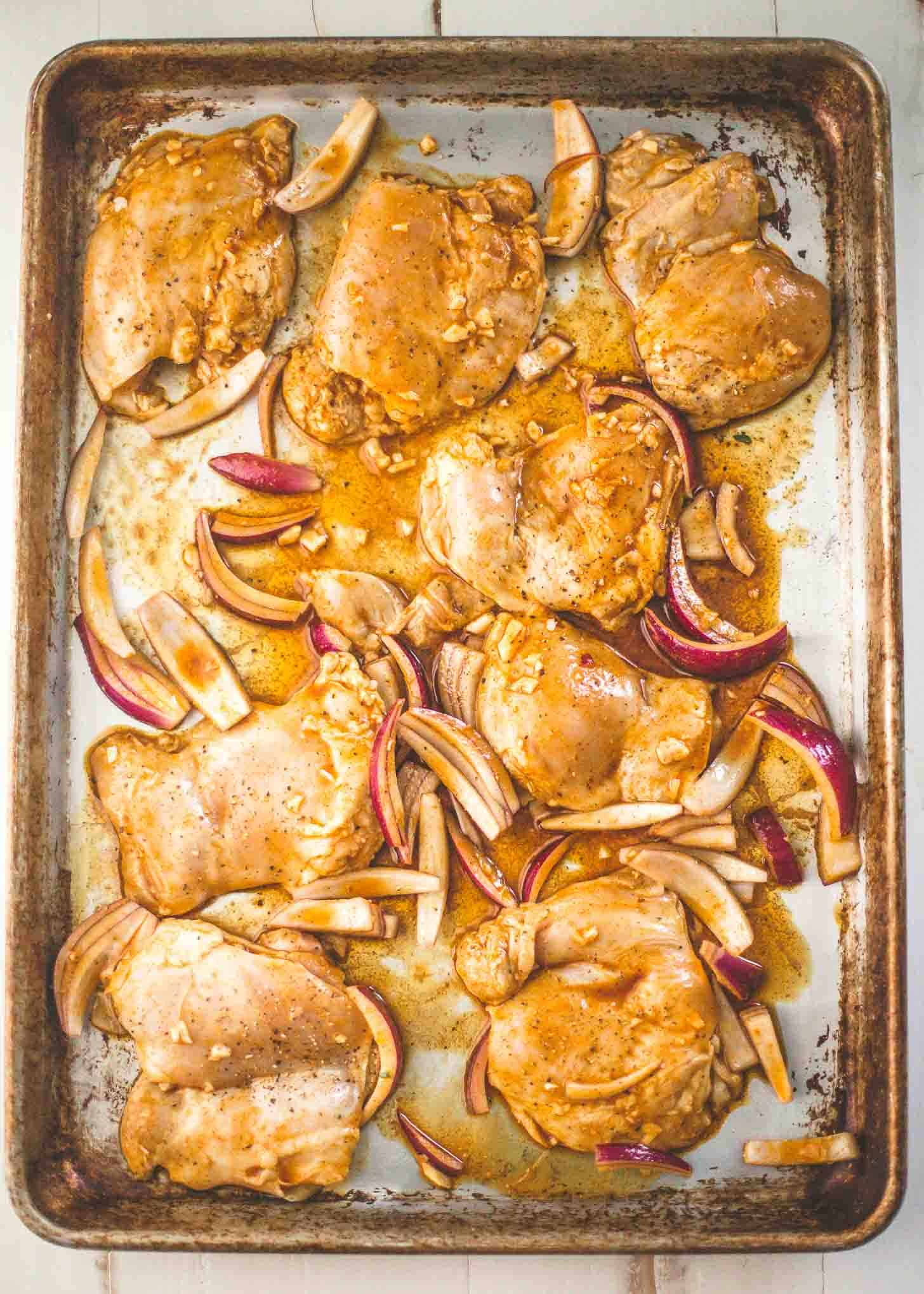 marinated chicken thighs and onions on a sheet pan