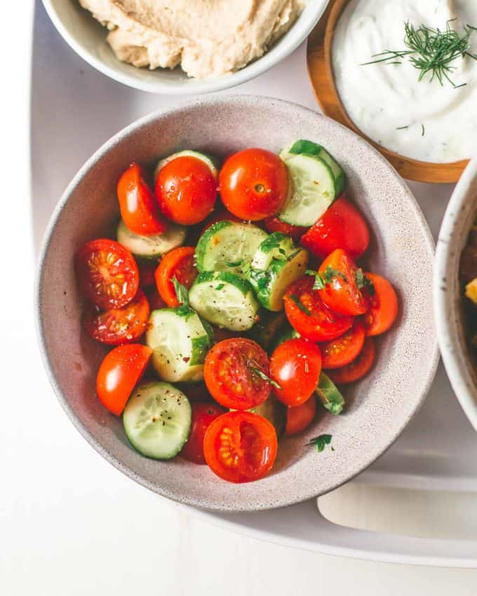 chopped tomatoes and cucumbers in a white bowl