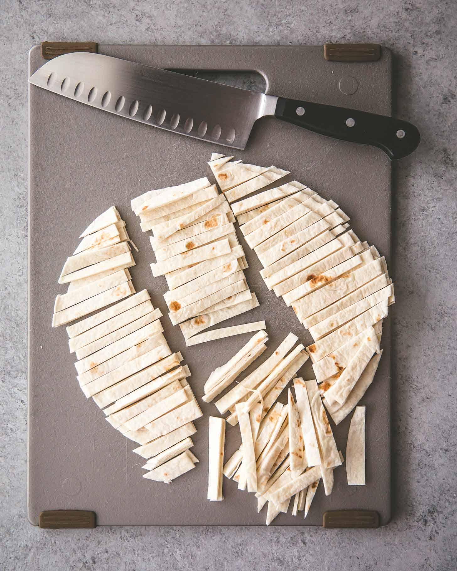 cutting tortillas into strips on a grey cutting board