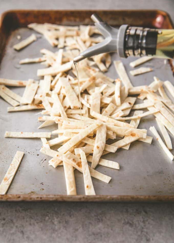 drizzling olive oil on tortilla strips