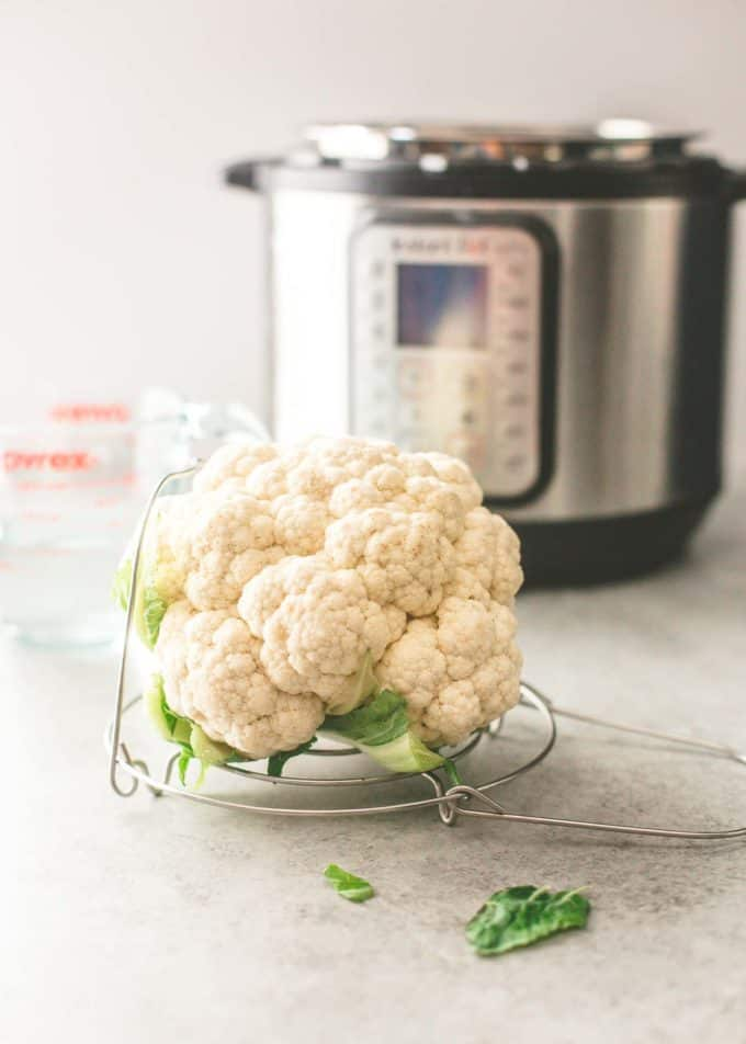 an uncooked head of cauliflower on a trivet for the instant pot