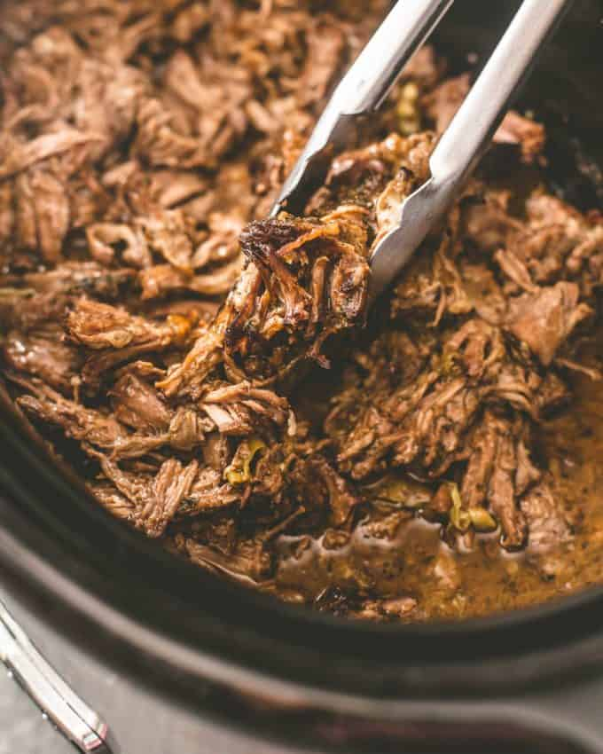 Slow Cooker Mississippi Roast in a slow cooker with tongs