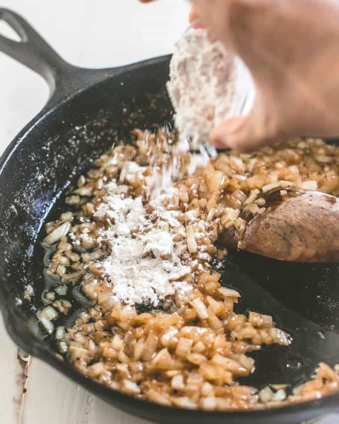 adding flour to onions in a skillet