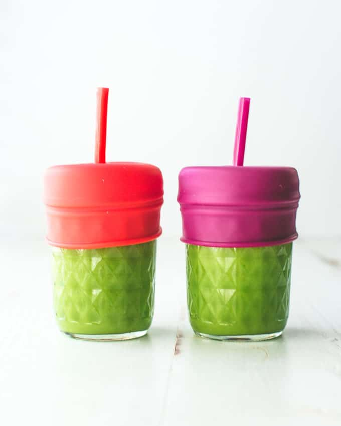 green smoothie in glass jars with straws