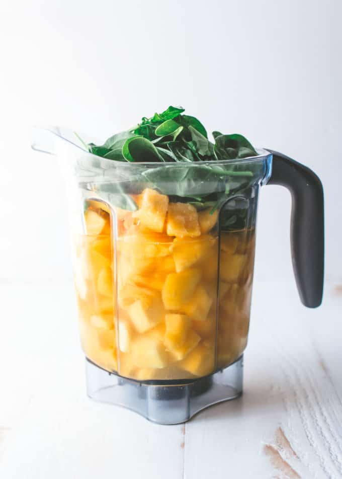 mango chunks and baby spinach in a blender