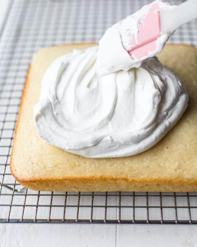 spreading vanilla frosting over a square vanilla cake