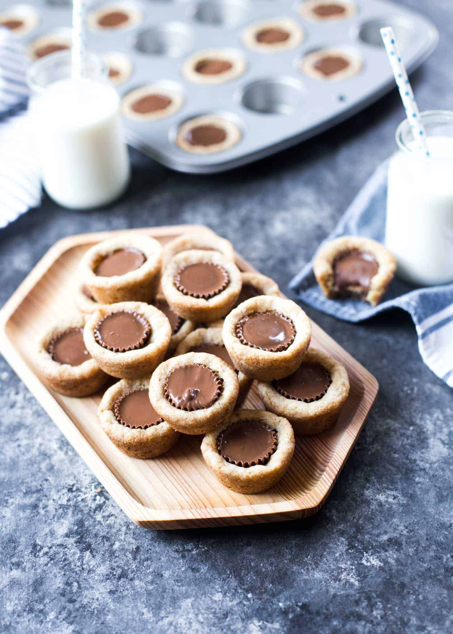 peanut butter cookie cups stacked on a wooden tray