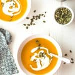 two bowls of butternut squash soup on a table