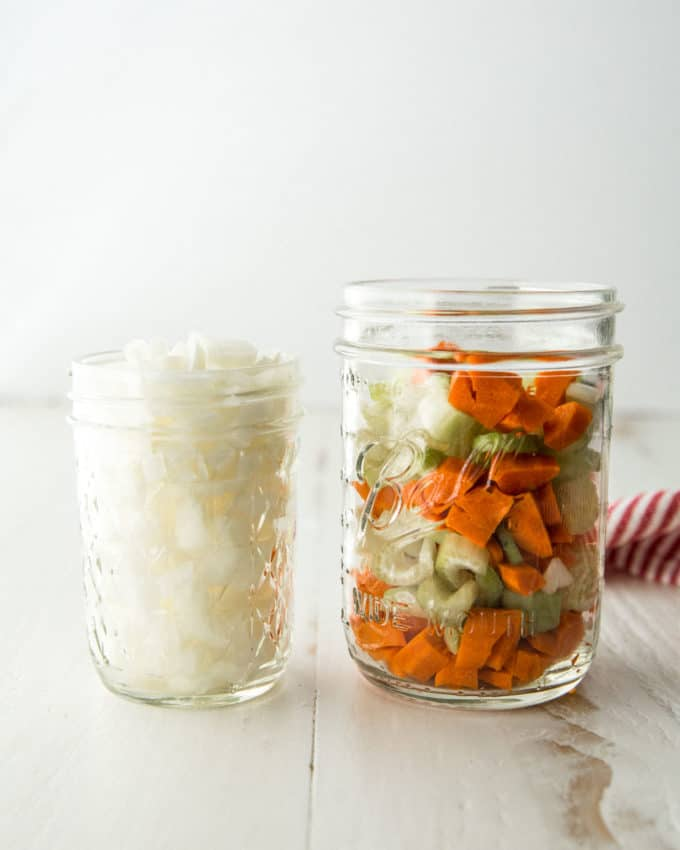 chopped onions and vegetables in mason jars