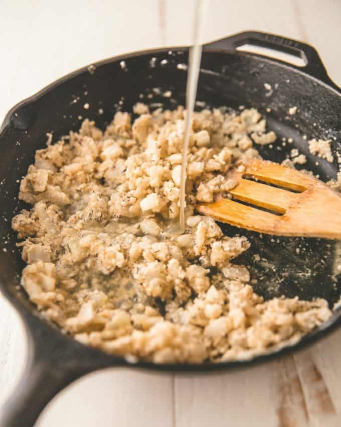 adding broth to onions in a skillet