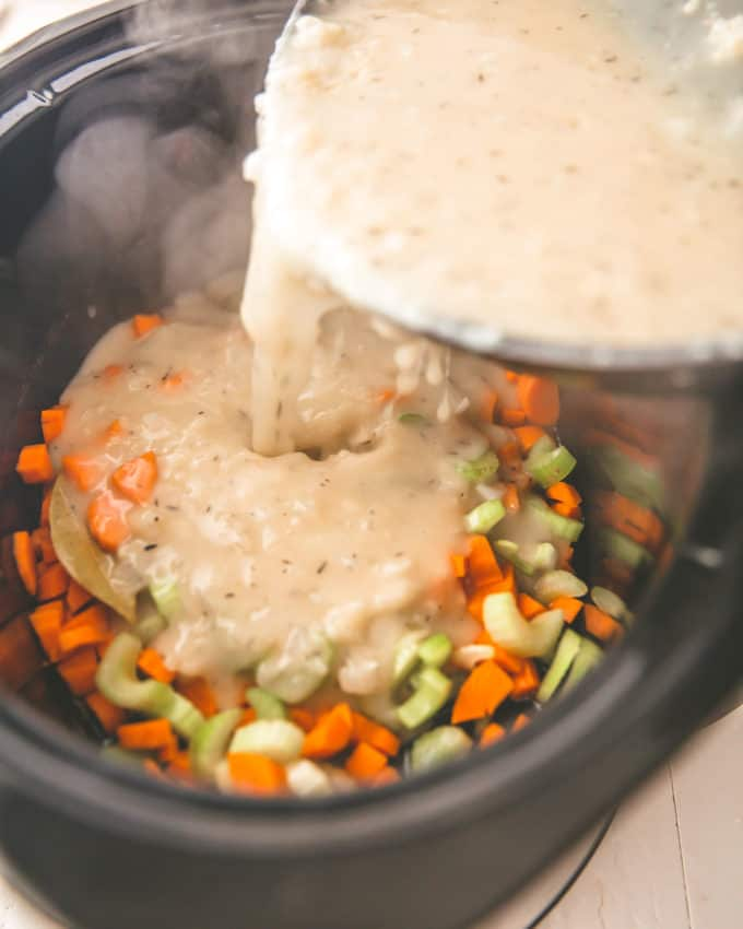 adding flour mixture to vegetables in a slow cooker