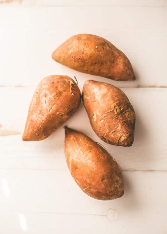 raw sweet potatoes on a white table