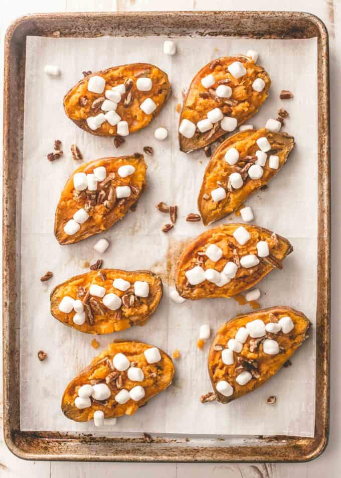 twice baked sweet potatoes on a parchment lined sheet pan