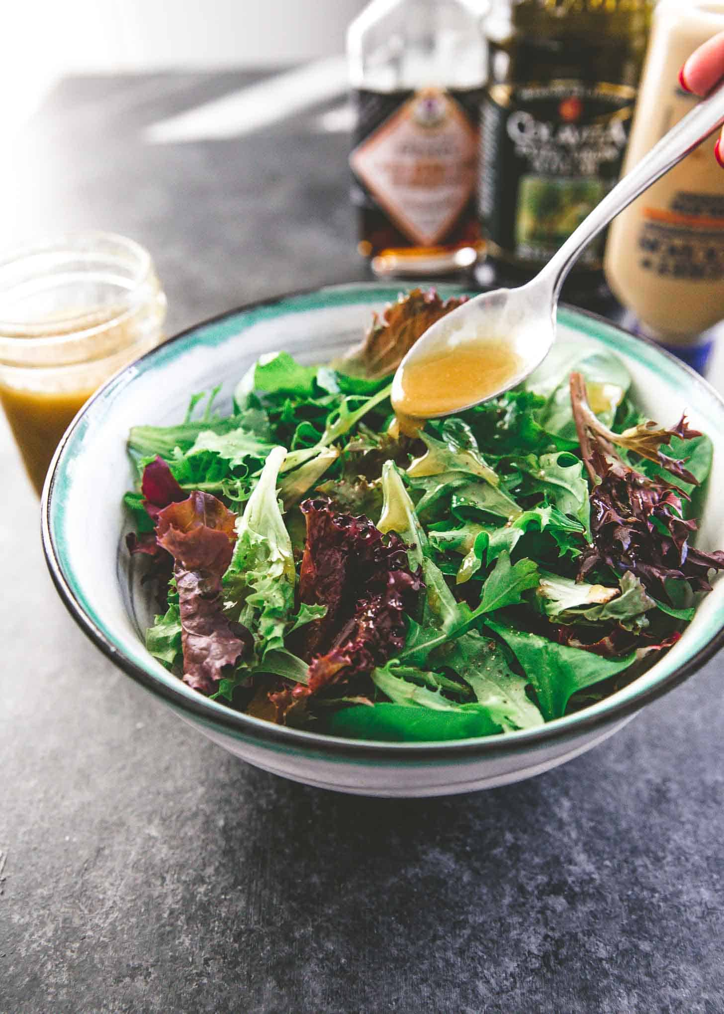 adding vinaigrette to salad