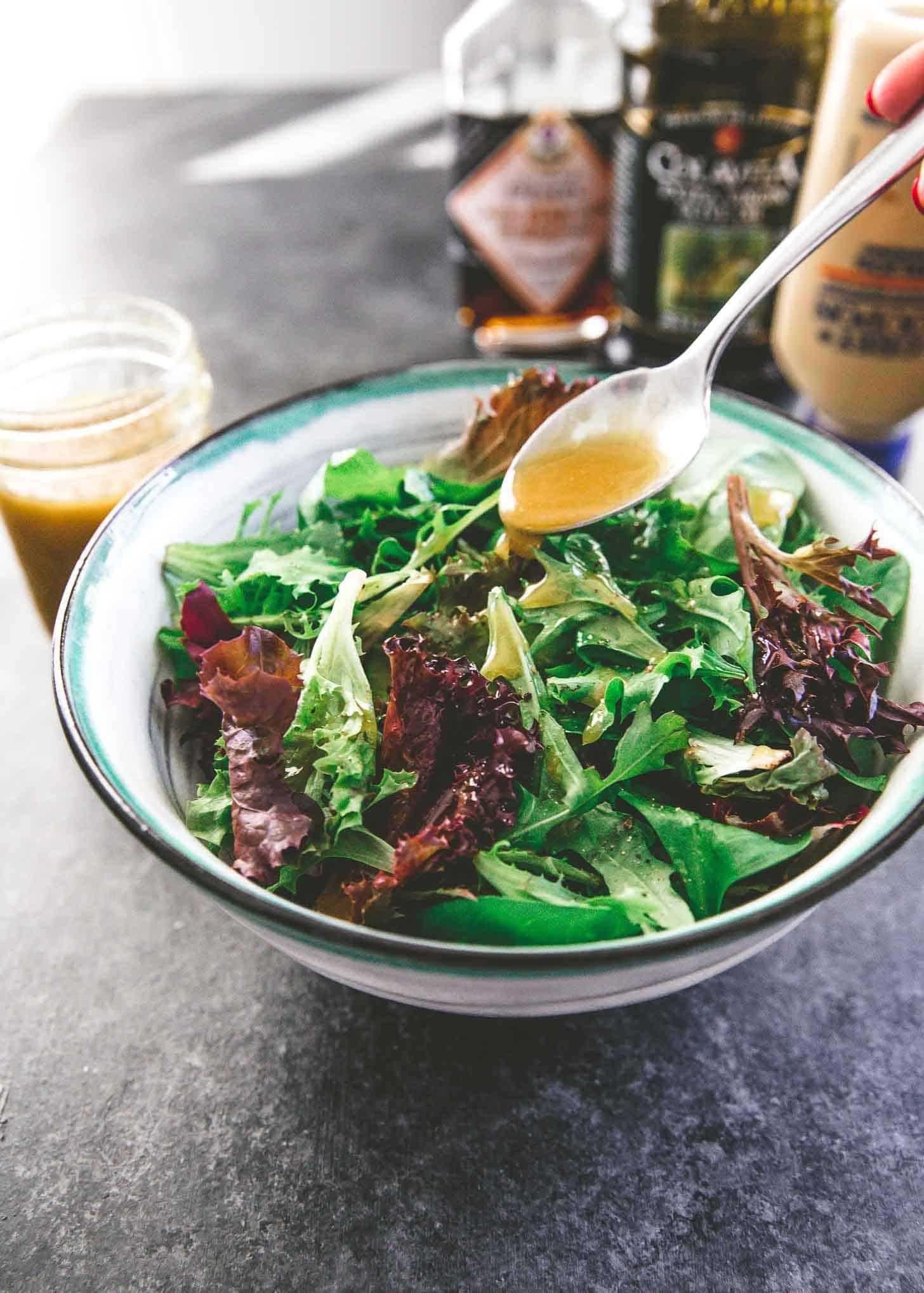 adding homemade vinaigrette to a salad