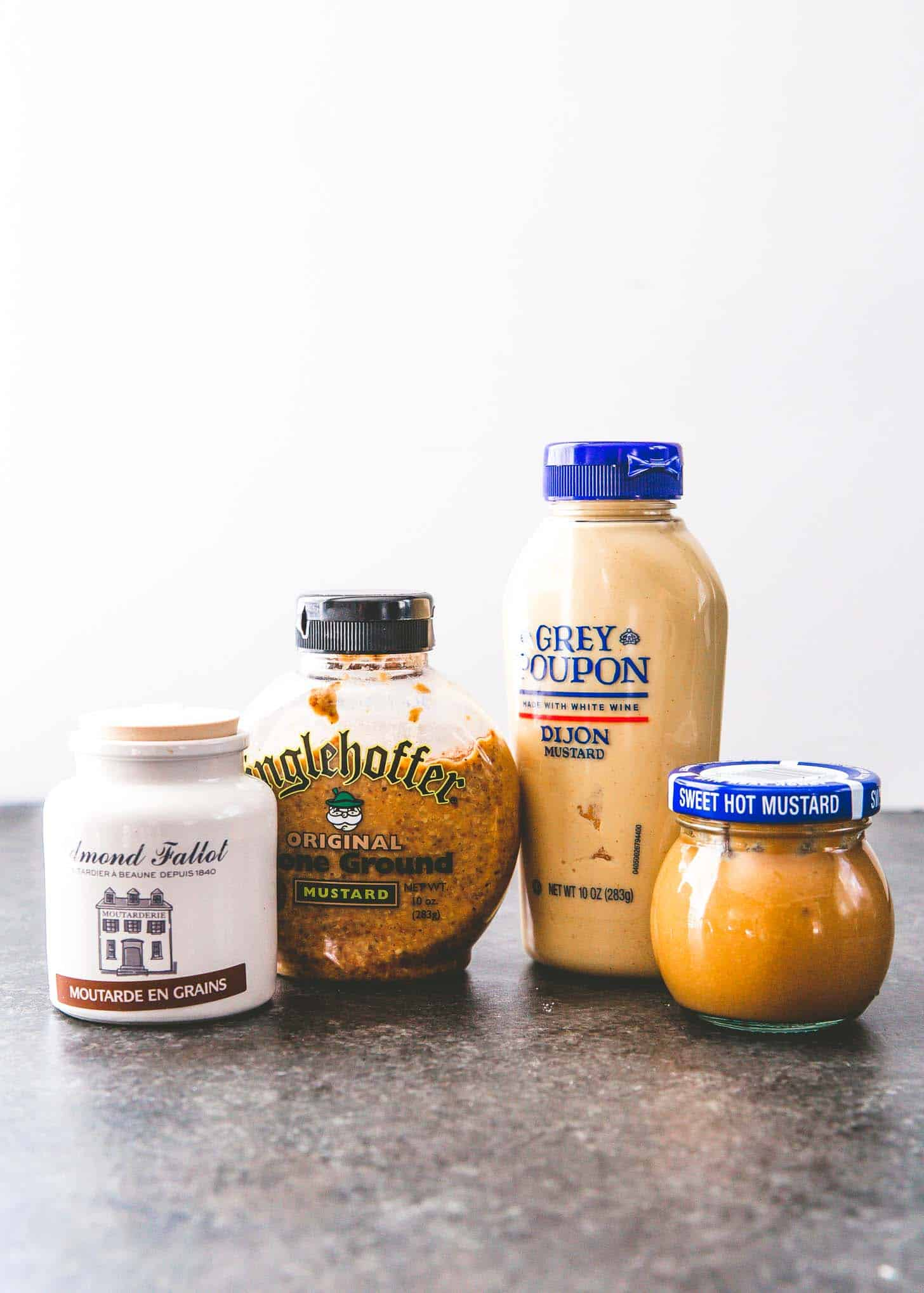bottles of mustard on a grey countertop