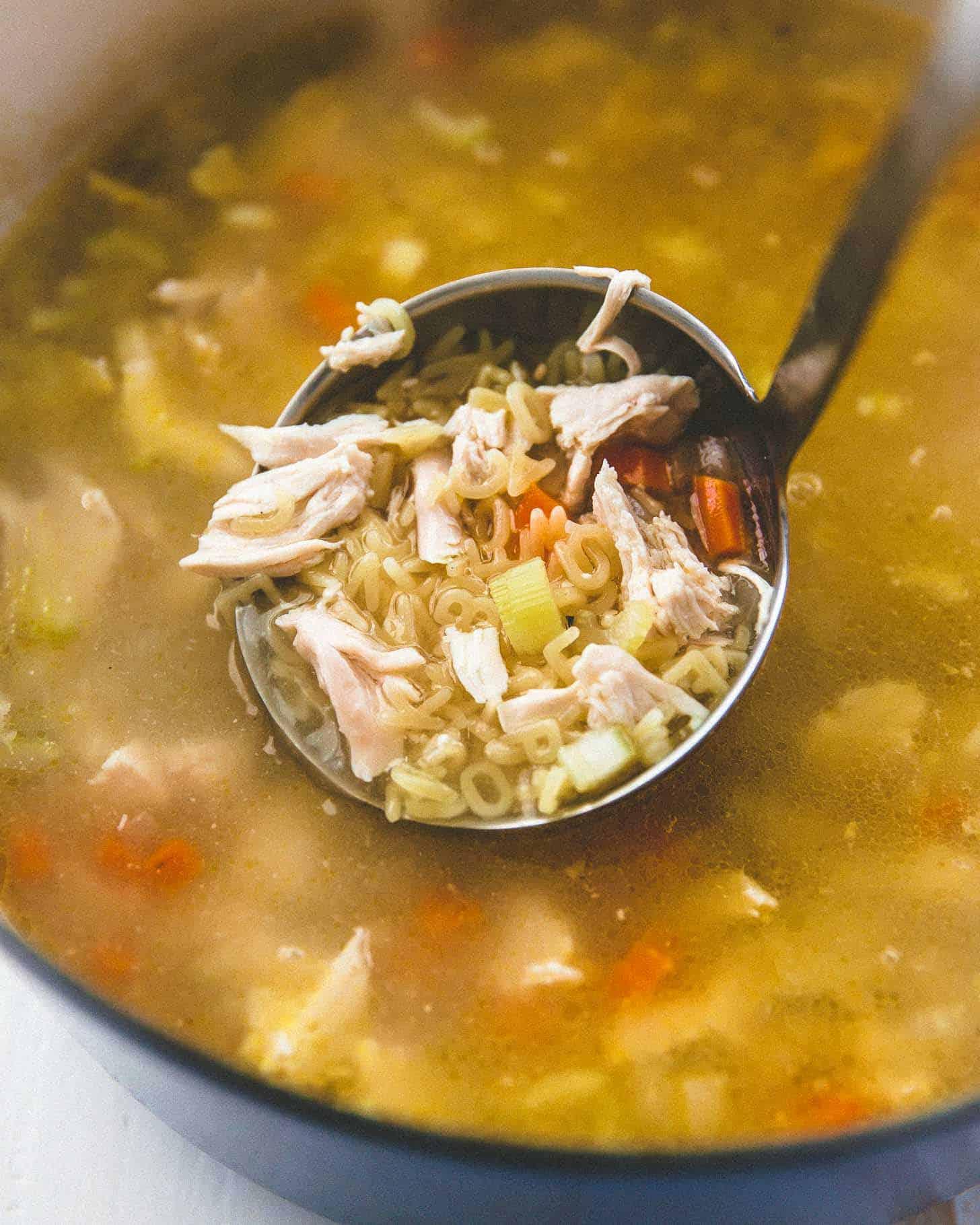 chicken noodle soup with miso in a ladle