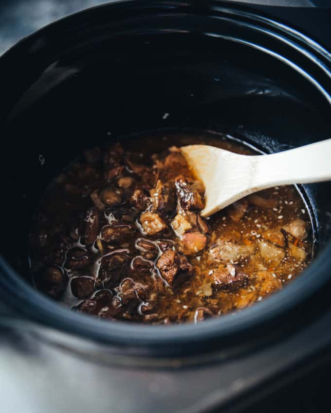 stirring beef in a slow cooker