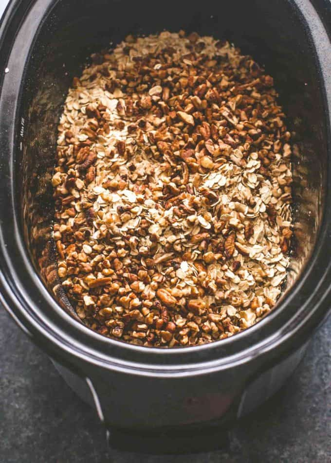 adding ingredients to granola in the slow cooker