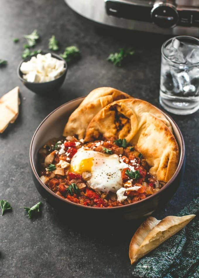 slow cooker shakshuka in a bowl with naan