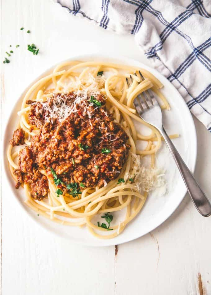 beef ragu over pasta on a white plate